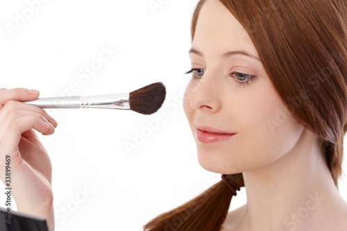 Teenage girl using makeup brush smiling