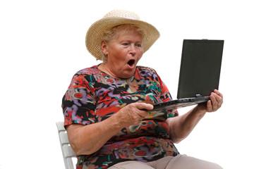 Seniorin mit einem computer vor weißem Hintergrund