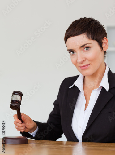 Portrait of a serious woman knocking a gavel