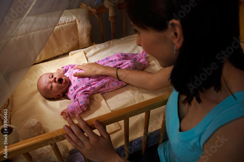 young mother sitting by the crib with 7 week old baby