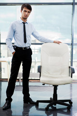 Portrait of confident businessman at his office standing near em