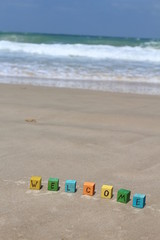 The word WELCOME written on colorful wood cubes, at the beach