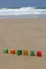 The word SUMMER - written on colorful wood cubes, at the beach