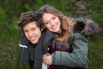 happy smiling winter teen couple in piggy back