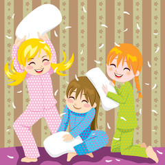 Three young girls having fun in pillow fight