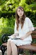 Junge Frau erholt sich lesend auf einer Parkbank