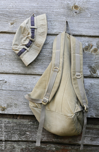 Khaki Hat and Backpack on the Wooden Wall