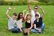 junge menschen sitzen jubelnd im park