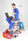 Man sitting on ladder with laptop and plumbing tools