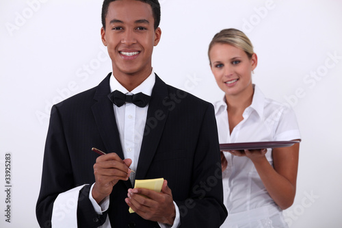 a young latino well dressed waiter writing order