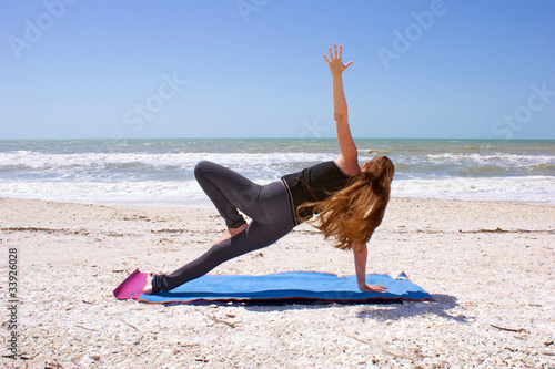 woman doing yoga exercise on beach in Vasisthasana or side plank