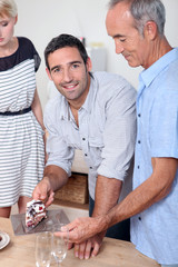 Man giving a slice of cake to his father
