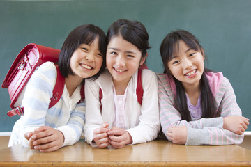 黒板の前で微笑む小学生女子3人