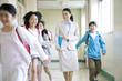 廊下を歩く女性教師とはしゃぐ小学生男女