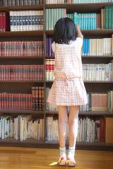 図書室で本を探す小学生女子の後ろ姿