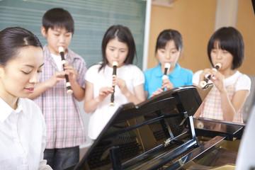 音楽室でリコーダーを吹く小学生4人