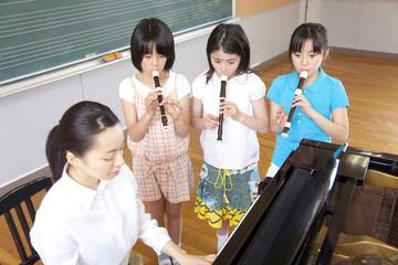 音楽室でリコーダーを吹く小学生