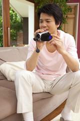 ビデオカメラで撮影する男性
