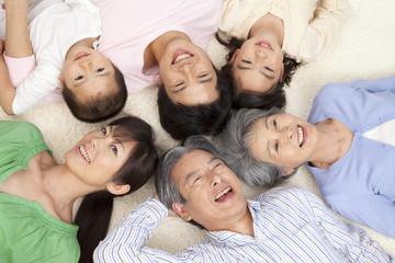 寝転がって微笑む親子3世代