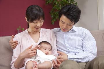 ソファに座る赤ちゃんと両親