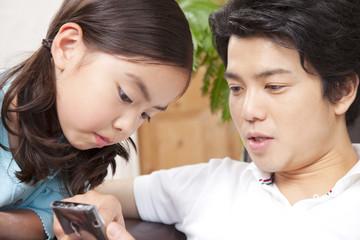 スマートフォンを操作する父親と娘