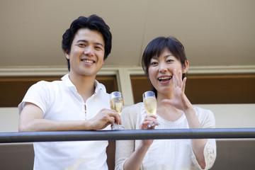 ベランダでシャンパンを飲むカップル