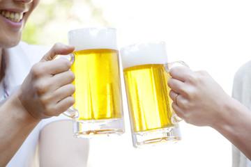 ビールで乾杯するカップルの手元