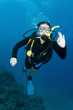 woman Scuba diver swims in clear blue ocean and makes OK sign