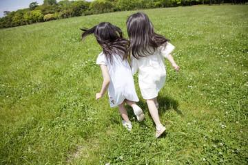 草原を走る女の子2人の後ろ姿