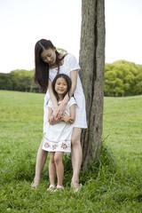 女の子を後ろから抱締める若い女性