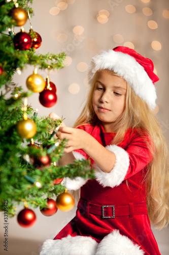 Fotobehang miss santa decorating the christmas tree