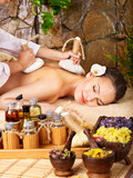 Woman getting thai herbal compress massage . - 33939877