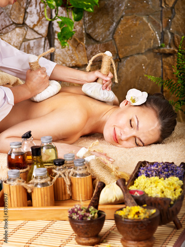 Woman getting thai herbal compress massage . © Gennadiy Poznyakov