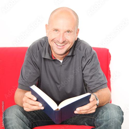 glücklicher Mann zuhause mit Buch