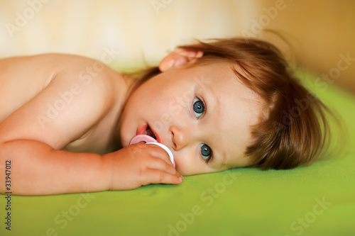 Cute baby girl with a soother in her mouth