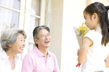 祖父祖母に花をプレゼントする孫娘