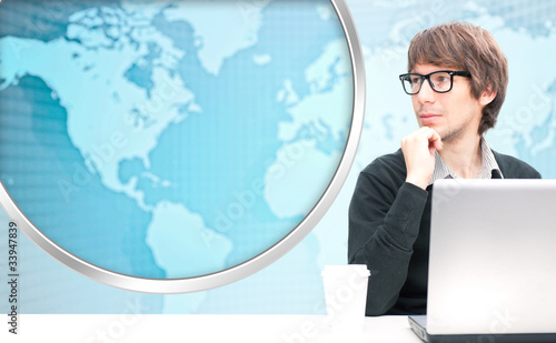 Portrait of happy young business man using her laptop. World map