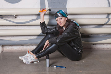 Young woman sitting against a brick wall with graffiti
