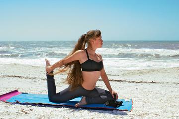 woman doing yoga exercise on beach in Kapotasana or King Pigeon
