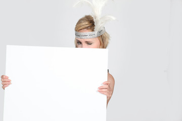 Blond woman holding message board with feathers in hair