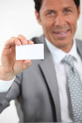 Man holding up a business card left blank for your image or text