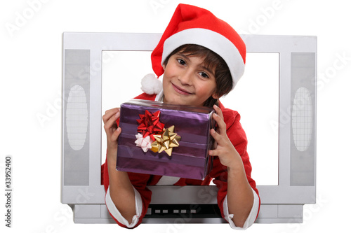 little boy dressed in Christmas clothes behind a screen