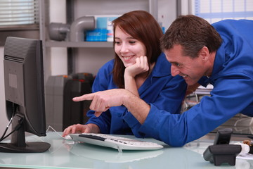 two colleagues in blue jumpsuit watching a computer