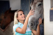 Blond teenage girl stroking horse
