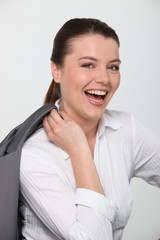 Laughing businesswoman with her jacket over her shoulder