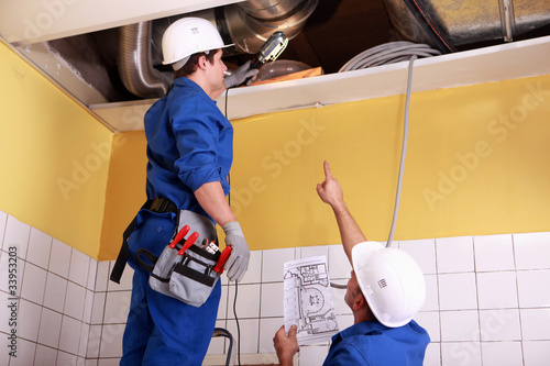two technicians checking the air conditioning in the ceiling