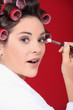 woman with curlers in her hair putting make up