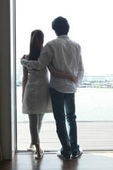 窓際で外を眺めるカップルの後姿