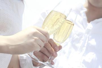シャンパンで乾杯するカップルの手元