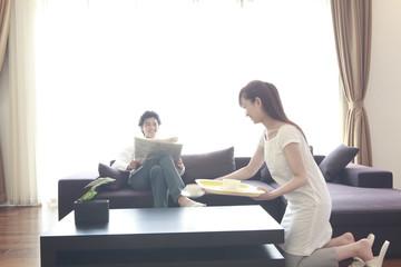 ソファで新聞を読む男性とコーヒーを運ぶ女性